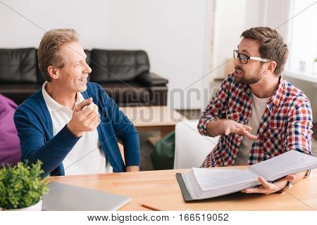 Hard working person. Handsome bearded young man holding a folder with documents and gesticulating while telling something to his male colleague