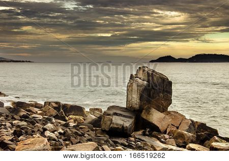 Large Pointed Stone Among The Rocky Formations By The Sea