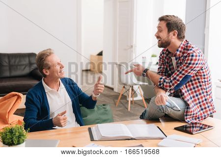 Pleasant interaction. Nice delighted positive men having smiling and chatting with each other while being in the office