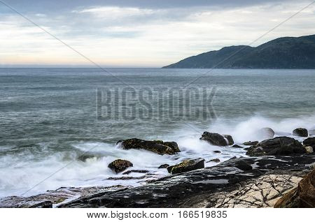 Water sea waves splashing on sea rocks. Horizon and a mountain on the background. Long exposure photo at Morro das Pedras Florianopolis Brazil.