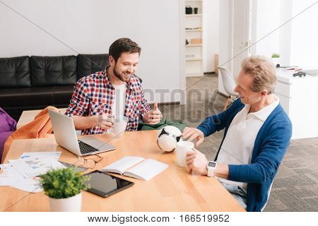 It is lunchtime. Delighted positive cheerful man holding cups and chatting with each other while having tea