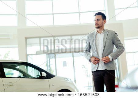 Smart salesperson at car dealership selling vehichles