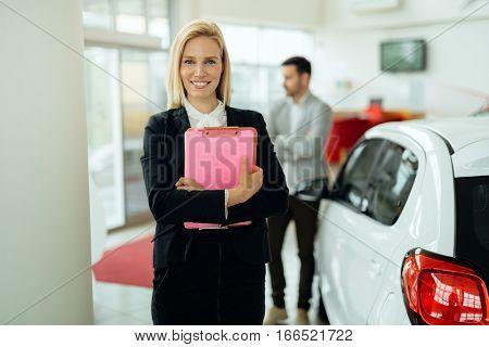 Smart salesperson selling cars at car dealership