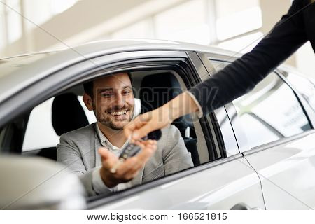 Salesperson selling cars at modern car dealership