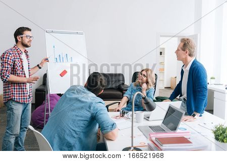 Statistical data. Serious young handsome man standing hear the whiteboard and presenting a diagram while presenting a report