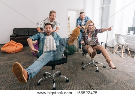 Fun at the office. Positive cheerful strong men pushing the office chairs and laughing while entertaining themselves