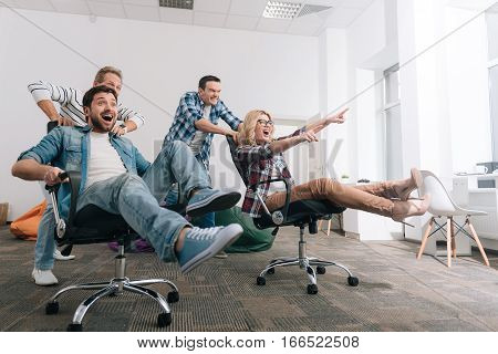 New sports activity. Happy positive joyful people holding their legs up and trying to keep balance while riding in the swivel chairs