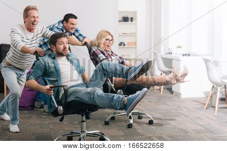 Extreme activity. Delighted carefree happy people riding in the office chairs and having fun while having a chair riding competition