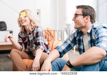 Guess my job. Delighted good looking nice man and woman wearing sticky notes on their foreheads and playing a name game while resting with their colleagues