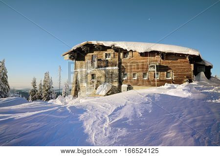 Mountain hut covered with snow in beautiful sunshine day.