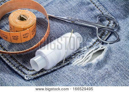 A spool of white thread with a tailor's tape measure and scissors on a background of denim