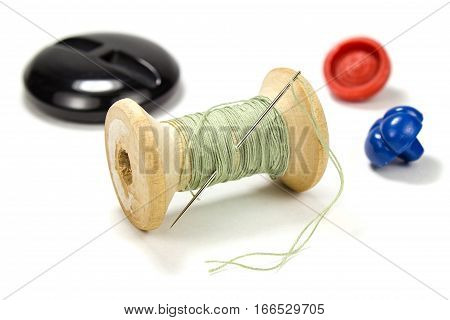 Vintage wooden spool of green thread needle and buttons on white background