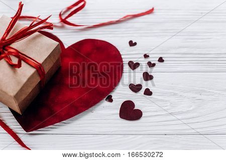 Happy Valentine Day Concept. Stylish Present And Velvet Hearts With Ribbon On Rustic White Wooden Ba