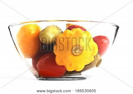 Assorted vegetables in a glass jar isolated on white background