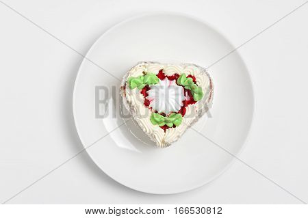 Cake in the shape of a heart on a plate isolated on white background