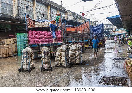 People Load The Trucks In Rain