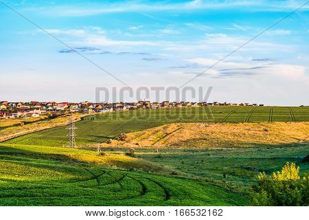 Hilly landscape with a green field and suburban houses on the horizon. Rural landscape in the Belgorod region Russia.