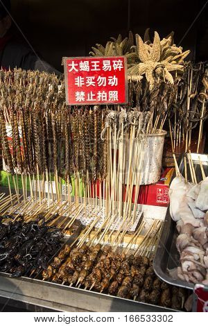 Beijing, China - December 31, 2016: Wangfujing food stall with foods like scorpions spiders, seahorses, and starfish on sticks for tourists.