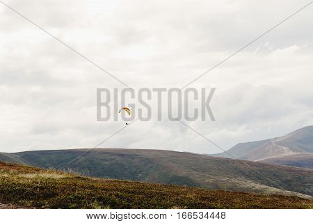 Parachute Skydiver Flying In Clouds At Mountains, Travel Adventure Concept, Space For Text