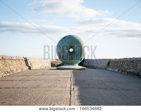 BRIGHTON, UK - 23 APRIL 2015: A view of the public artwork titled 'Afloat' by artist Hamish Black located on Brighton seafront UK. The sculpture is a circular donut shaped globe cast in bronze with a natural blue/green patination.