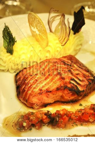 salmon roasted on fire and smashed potato with sauce