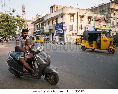 Chennai India - 24 March 2015: Candid urban street scene on the hot streets of Chennai India with a father driving a moped with his daughter in front of him. Tuk Tuks (motorised rickshaws) visible in the background.