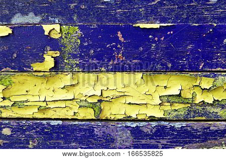 Texture background - old painted wooden surface with peeling purple and yellow paint - texture colorful background. Colorful texture wooden background