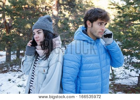 Boyfriend and girlfriend couple are talking on the phone while they are on a date in the mountains on a snowy day. They are bored and pass from each other.
