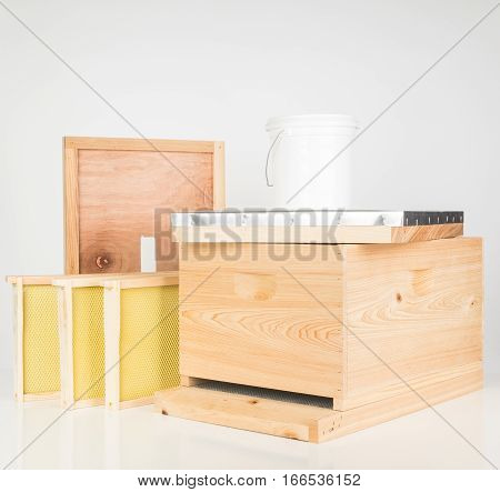 New starter kit cypress wooden honey bee hive with a few frames and syrup feeding bucket.
