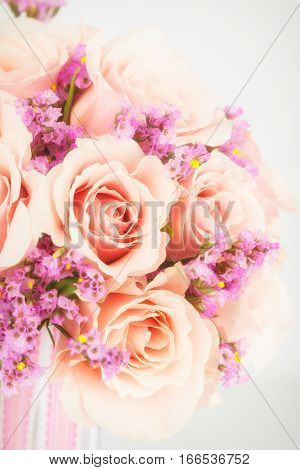 Close up view of wedding bouquet of pink statice and coral roses