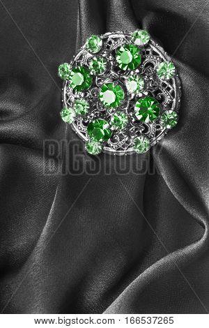 Vintage emerald brooch on black satin closeup