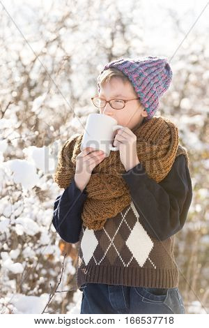 small boy or cute nerd kid in glasses hat sweater and fashionable knitted scarf holds cup and drinks in sunny winter outdoor on natural background