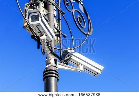 Security camera surveillance on the urban street lamppost on a background of blue sky. The color image. Big Brother is watching through camcorder lens.