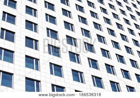 A wall with a lot of square glass windows on the building. The rhythm of the windows. Geometric pattern