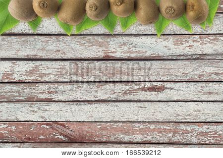 Juicy kiwi fruit on wooden background. Kiwi fruit at border of image with copy space for text. Top view.