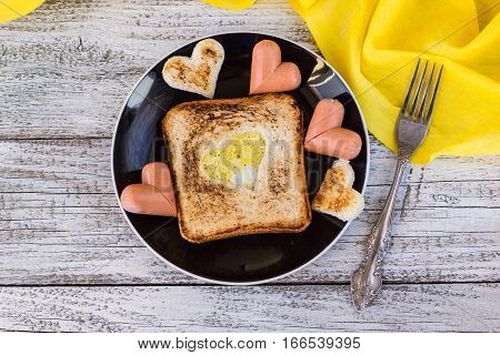 breakfast for the celebration of Valentine's day - toast with scrambled eggs in the form of hearts sausages in a plate and a fork