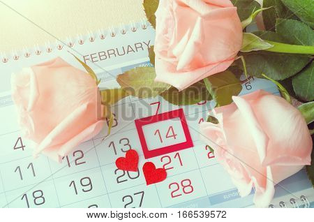 St Valentines day background - roses of light peach color and two red hearts on the calendar with framed St Valentines day date February 14. St Valentines day card with retro tones applied. Concept of St Valentines day celebration