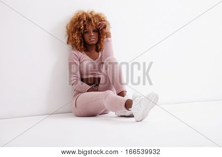 serious black blonde woman sits on the floor