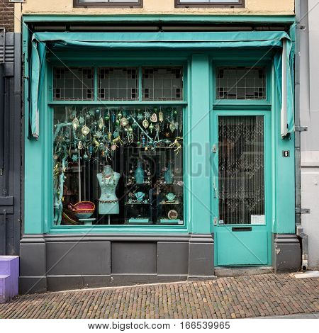 NIJMEGEN NETHERLANDS - 19 JUNE 2016: The facade to a junk shop in the Dutch town of Nijmegen only selling bric-a-brac of a turquoise blue color.