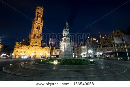 BRUGES BELGIUM - 20 JUNE 2016: Wide angle night view of the central market place in the Belgian town of Bruges with the Belfort visible in the distance and the statue of local heroes Jan Breydel and Pieter de Coninck in the foreground.