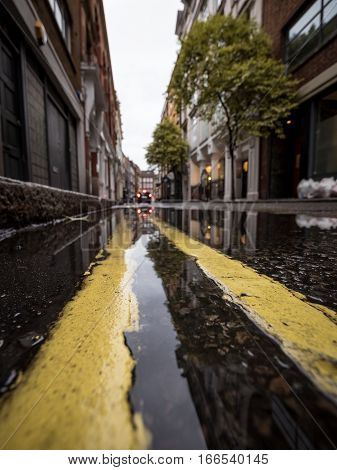 Shallow foreground focus on the kerbside puddle reflecting a typical London back street.