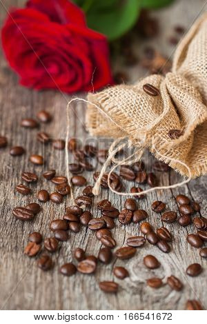 Roasted coffee beans, fresh red rose, coarse burlap sac on old wooden table. Vintage still life. Place for text. Top view. Concept romantic morning with your favorite. Top view