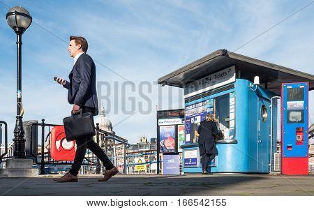 LONDON UK - 2 NOVEMBER 2016: A business commuter walking past the ticket office to the Bankside river bus ticket office. St. Paul's cathedral is visible in the background.