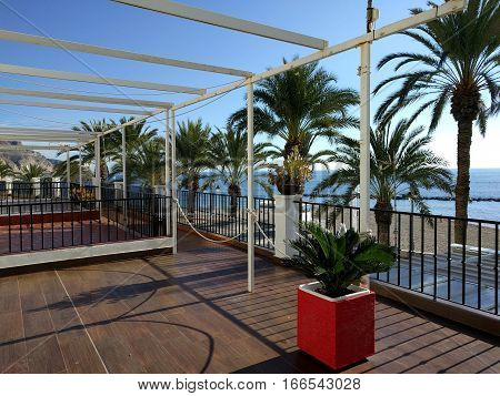 View to the beach and Mediterranean Sea through the terrace in Aguadulce. Aguadulce is a spanish locality of Roquetas de Mar province of Almeria. Spain