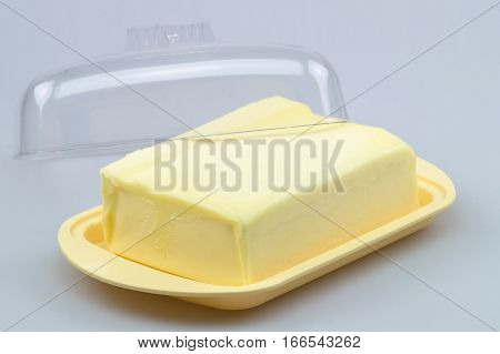 Butter on yellow butter dish on white background