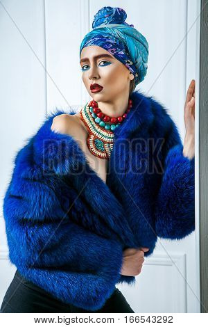 Beauty Portrait Of Fashion Model With Colored Headwear, Blue Fur Coat Red Eyebrow And Lips Makeup An