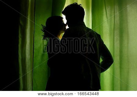 Silhouette Of Couple Standing At Green Curtains At Window And Hugging