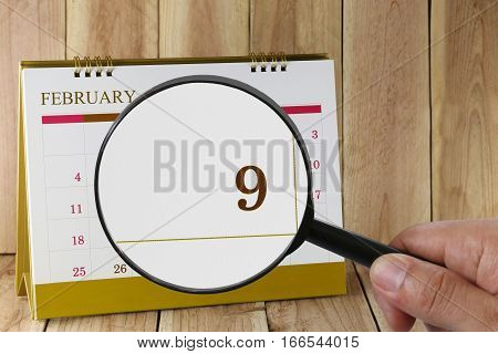 Magnifying glass in hand on calendar you can look ninth day of monthFocus number nine in FebruaryConcept in business and meetings.