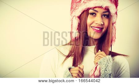 Clothing fashion people concept. Mulatto woman in winter outfit. Attractive lady has fur cap. Studio shot.