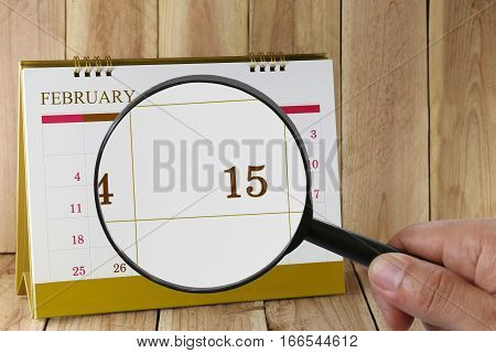 Magnifying glass in hand on calendar you can look Fifteenth day of monthFocus number fifteen in February Concept in business and meetings.